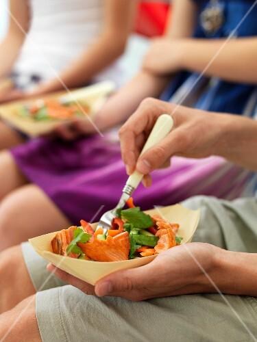 People eating noodles with teriyaki salmon