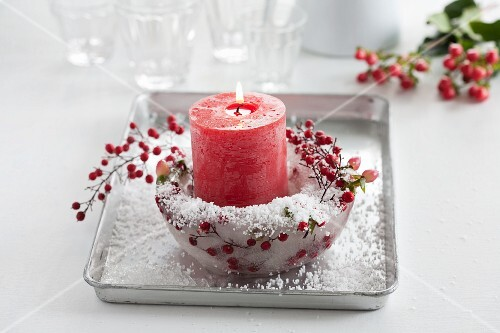 Red candle in ice bowl with St. John's wort berries, Skimmia japonica berries and artificial snow