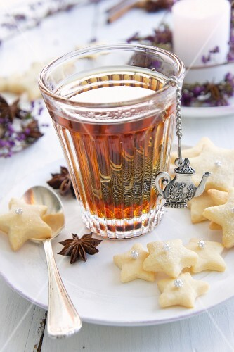 Black tea in a tea glass with a tea egg with star-shaped biscuits