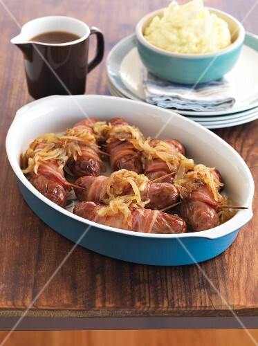 Pigs in blankets (sausages wrapped in bacon) with caramelised onions