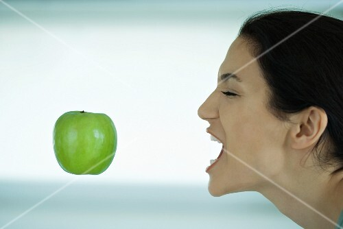 A young woman attempting to catch an apple in her mouth
