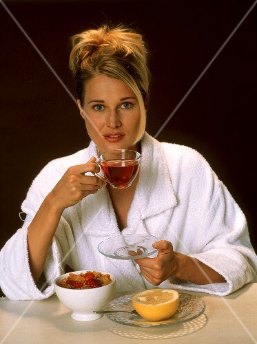 Woman at breakfast with tea, cornflakes and grapefruit