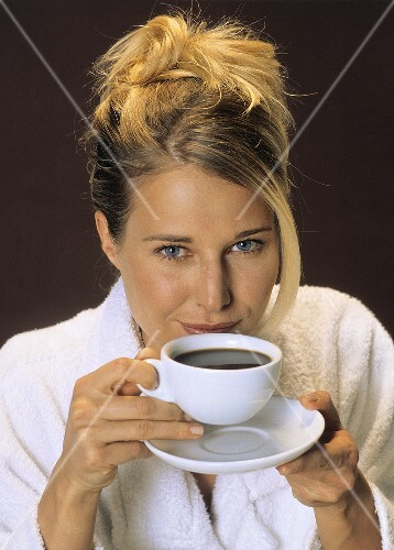 Blond woman in bathrobe holding coffee cup in her hands
