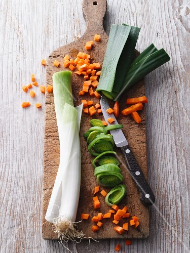 Sliced carrots and leek on a chopping board