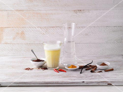 An Almased shake in a glass, a carafe of water and spices