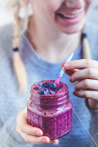 A woman with a blackberry and blueberry smoothie