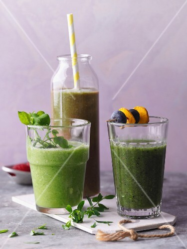 Three green smoothies garnished with chickweed and skewers