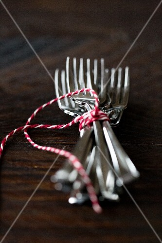 Forks tied with string on a wooden surface