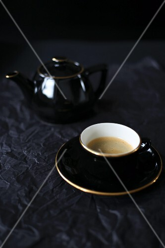 Coffee in a black cup and a jug