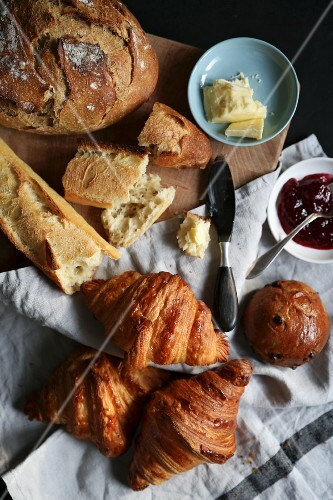 Various French breads with butter and jam
