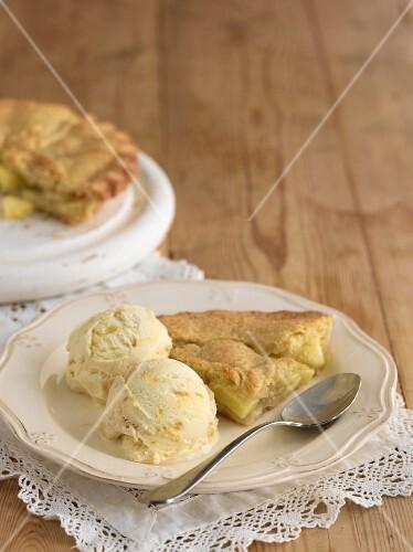Apple pie with vanilla ice cream on an old wooden table