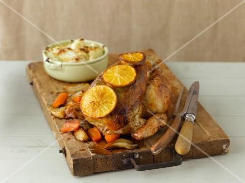 Roast chicken with lemon on a rustic wooden board
