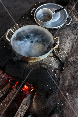 Noodles cooking in a pot over a rustic fire pit at a market in Vientiane, Laos