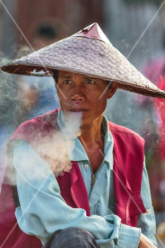 A thoughtful-looking man having a cigarette break at a market in Vientiane, Laos