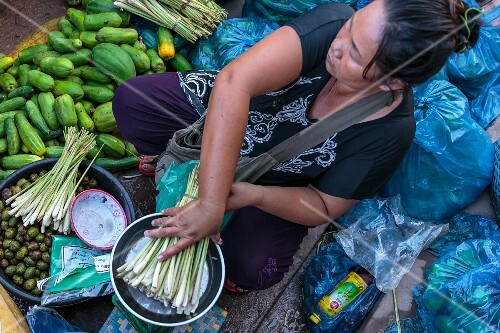 A market woman weighing a bundle of lemongrass at a market in Vientiane, Laos