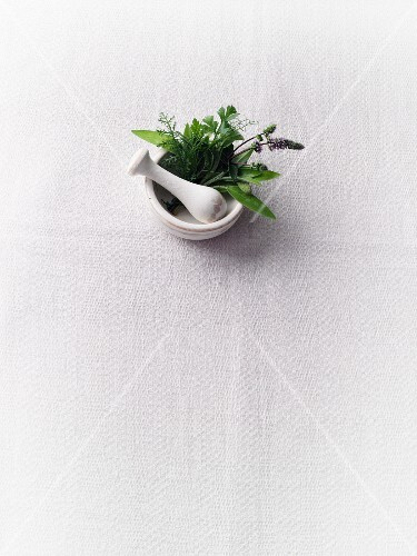 Herbs in a mortar on a white surface