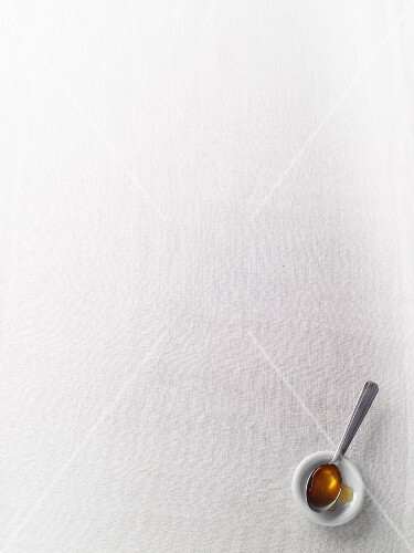A spoonful of honey on a white surface