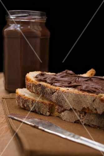 Chocolate spread in a jar and on bread
