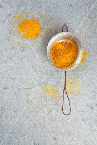 Curry powder in a metal sieve