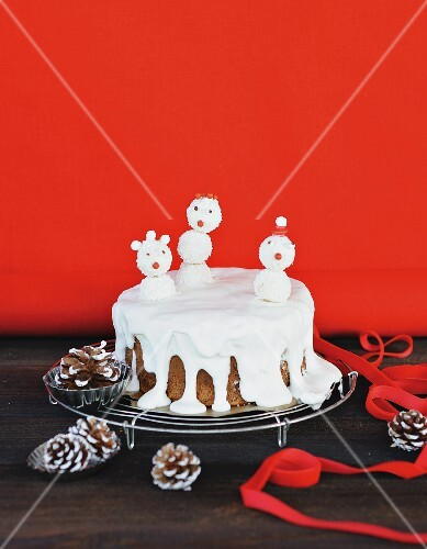 A snowman cake on a wire rack