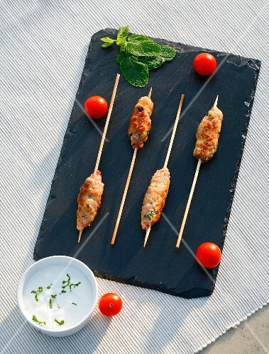 Minced meat skewers with yoghurt sauce and tomatoes
