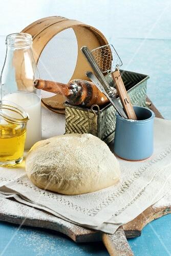 An arrangement of baking utensils, bread ingredients and bread dough