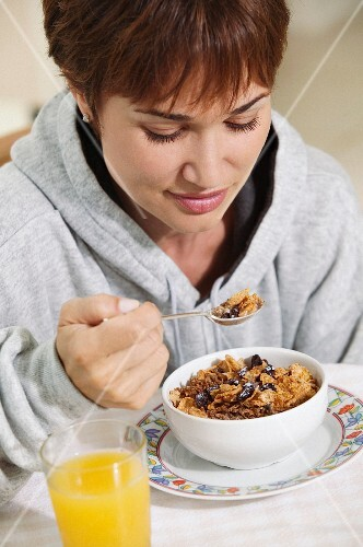 A woman wearing a hoodie eating wholemeal cornflakes