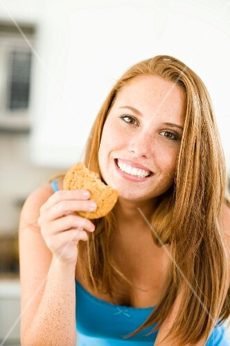 A young woman eating a cookie