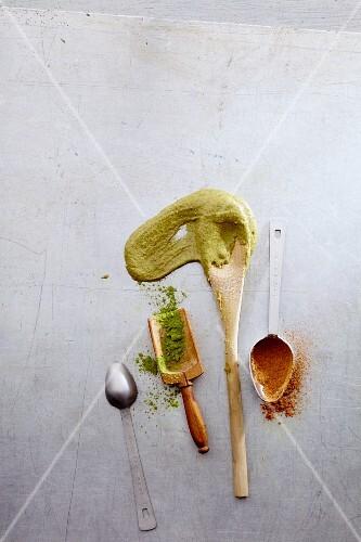 Kitchen utensils with raw batter, matcha and ground cinnamon