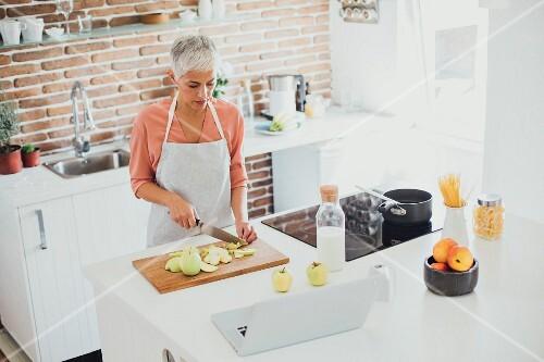 An older woman cutting apples in a modern kitchen
