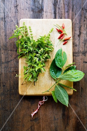 Lemon basil, aa sprig of green peppercorns and red chilli peppers