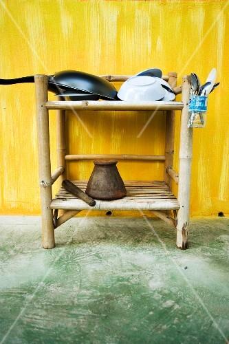 Oriental kitchen utensils on a small wicker shelf