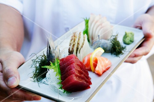 A chef holding a serving platter of fresh sashimi (Japan)