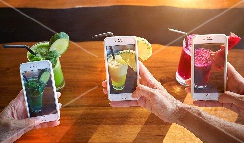 Three people taking photographs of cocktails with smart phones