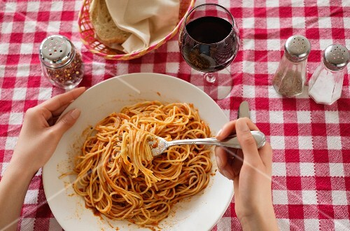 A person eating spaghetti with tomato sauce