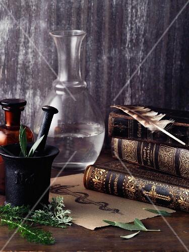 An arrangement featuring a book, a linen cloth, a quill and a Aesculapian staff
