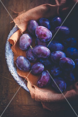 Damsons in a bowl on a brown cloth