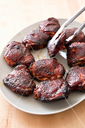 Grilled chicken thighs on a serving platter with a pair of tongs