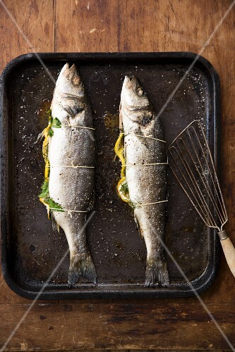 Two whole branzini on a baking tray stuffed with lemons and herbs, ready to roast