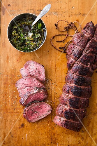 Smoked beef fillet on a chopping board next to a bowl of chimichurri sauce