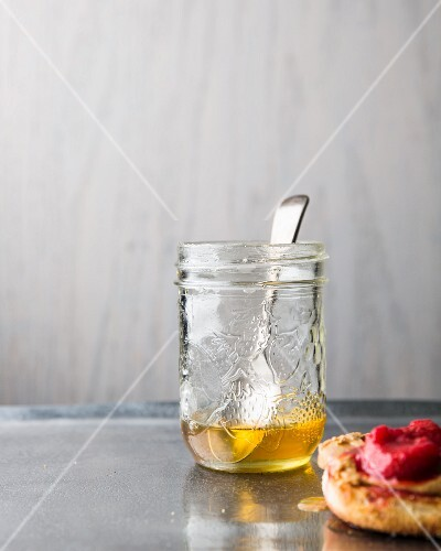 Honey in a jar with a spoon and an English muffin with raspberry jam