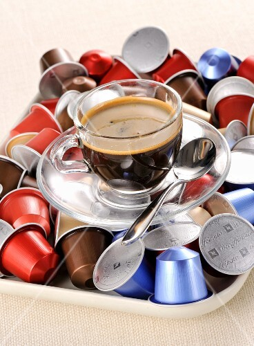 A cup of coffee and coffee capsules