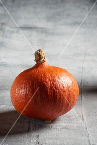 A Hokkaido pumpkin on grey surface