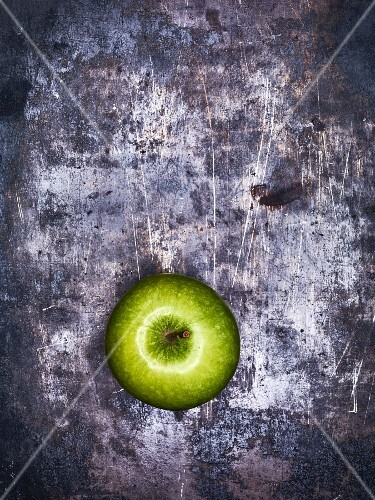 A green apple on a metal surface