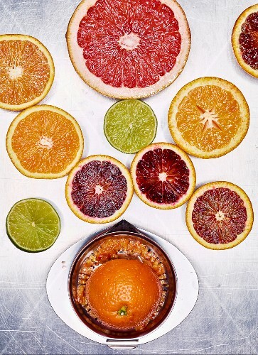 Various citrus fruits and a stainless steel juicer on a metal surface