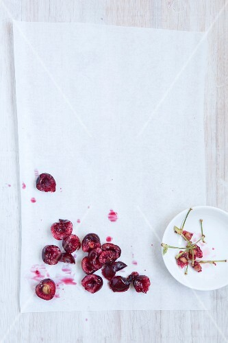 Pitted cherries on a white surface