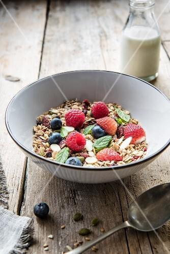A bowl of nuts, seeds and fresh fruit with milk in the background