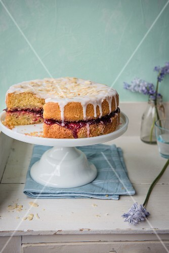 Almond sponge cake with cherry jam on a cake stand