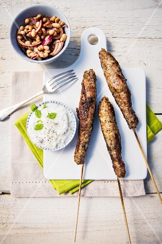 Lamb and mint kebabs with tzatziki and a bean salad