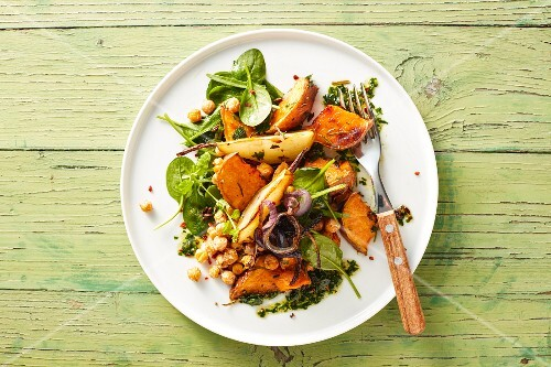 Oven roasted vegan vegetables with sweet potatoes, pears, chickpeas and herb pesto